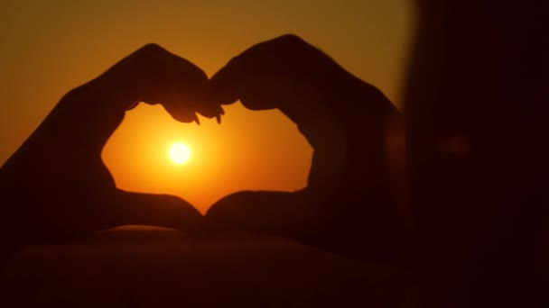 hands show heart on a fiery sunset sun