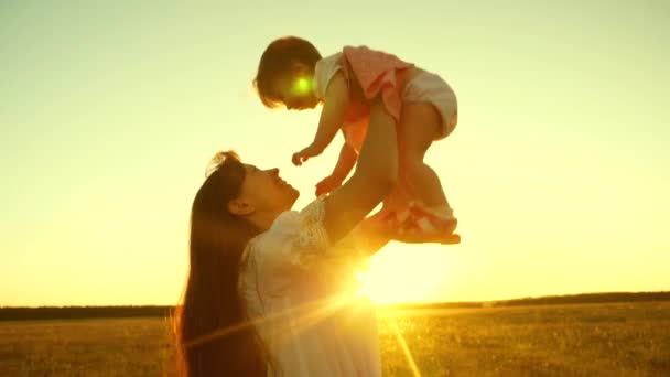 Mom throws happy daughter and kisses in sun, mother plays a small child at sunset
