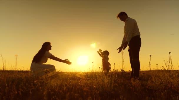 ein kleines Kind lernt, mit Mama und Papa zu gehen, junge schöne Familie im Feld mit Kind bei Sonnenuntergang, Zeitlupe