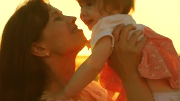 Mladá a krásná matka s dítětem hraje ve vzduchu v záři zapadajícího slunce zlaté slunce a směje se. Zpomalený pohyb.