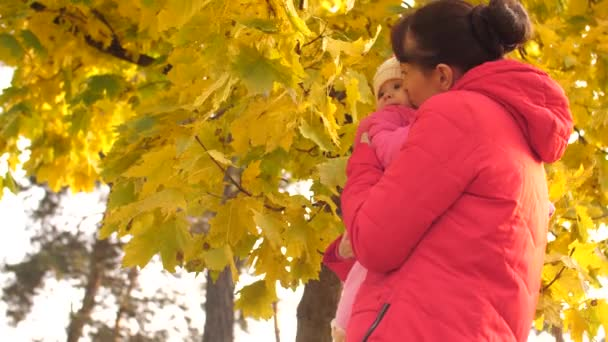 Baby with her mother is looking at autumn leaves, kissing with her mother.