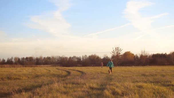 Děti pobíhat a hrát si s psa na podzimní pole pod modrou oblohou