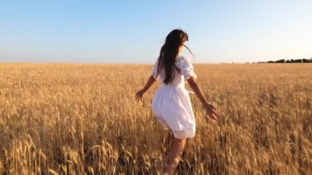 happy girl dancing in white dress on a field of ripe wheat, slow motion