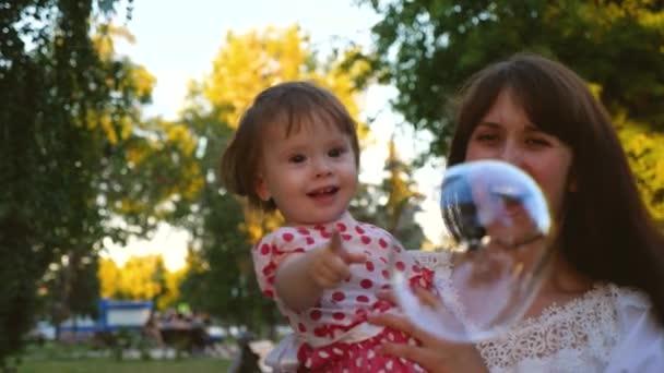 Maminka s malým dítětem praskne její ruce s velkými transparentní mýdlové bubliny, smích a úsměv. Zpomalený pohyb