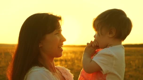 Mom is talking with happy baby, baby is sitting on mothers arms at sunset of the golden sun. Slow motion.