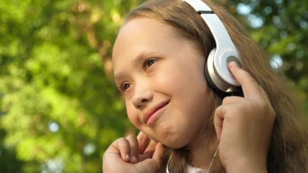Girl in headphones listening to music and smiling dancing in summer park