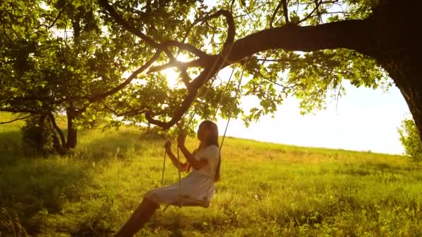 Happy girl with long hair, swinging on swing in bright rays of golden sunset and smiling. Slow motion
