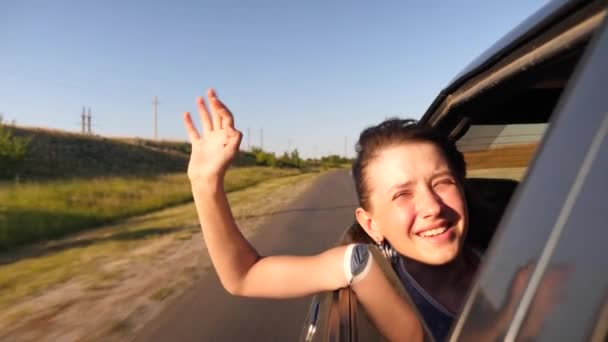 Beautiful girl rides in the car with her hands in the window, and smiles waving her hand in the bright light of the golden sun. Slow motion.