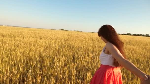 Dívka s dlouhými vlasy běží přes pole s pšenicí, miloval jednu ruku a smích.