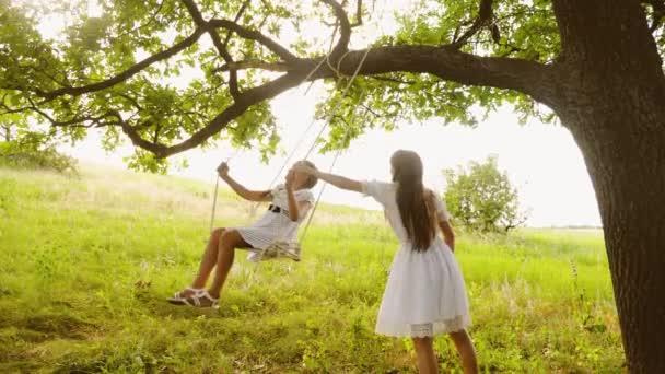 Šťastné děti houpat na houpačce pod strom letní dub a smích. Dospívající dívky hrají spolu v přírodě a úsměv