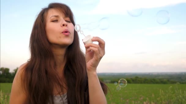 Beautiful girl with long hair blowing transparent soap bubbles against the blue sky and smiling. Slow motion.