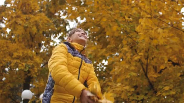 Girl is throwing autumn leaves upwards and smiling. Slow motion.