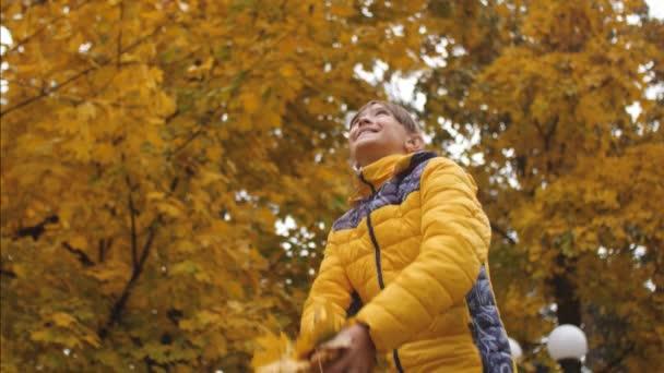 glückliches Mädchen wirft im Herbst gelbe Blätter in den Park und lächelt. Ahornblätter fallen vor dem Hintergrund gelber Bäume langsam zu Boden. Zeitlupe.