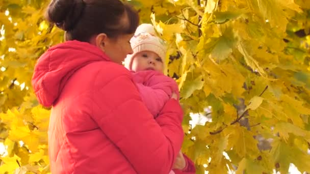 Mother holds baby in her arms and kisses him on cheek, shows yellow leaves to child and laughs.