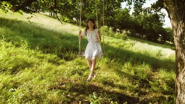 girl with long hair in white dress laughs rolling on swing under