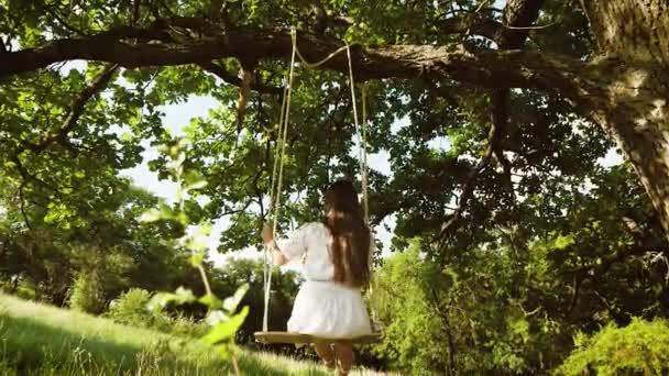 girl with long hair in white dress riding on swing under an oak tree in park in autumn. View from the back. Slow motion.