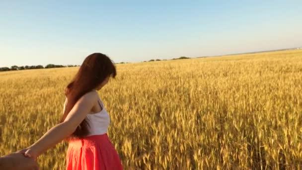 dívka běží přes pole pšenice drží její milovaný mans ruku. Zpomalený pohyb.
