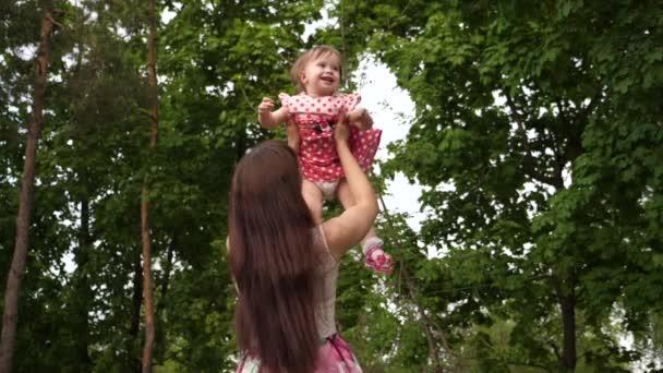 Dítě se směje s její matkou, létání ve vzduchu. Dítě s úsměvem, hraní a procházky se svými rodiči v parku. Zpomalený pohyb