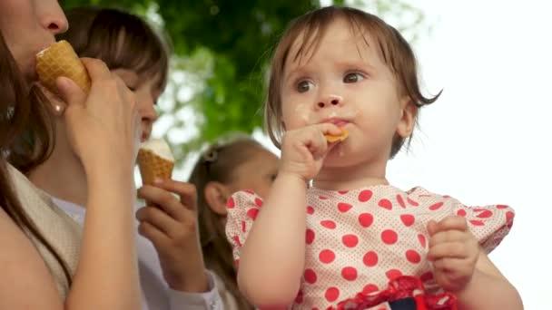 Holčička je jíst zmrzlinu sedí na lavičce v parku se svou rodinou