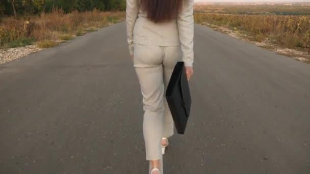 obchodní žena s černou aktovkou kráčí ve světle obleku a bílé boty s vysokými podpatky jsou procházky po asfaltu s odznaky, pohled zezadu
