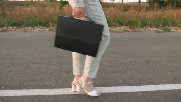 obchodní žena s černou aktovkou kráčí ve světle obleku a bílé boty s vysokými podpatky jsou procházky po asfaltu s odznaky, zblízka