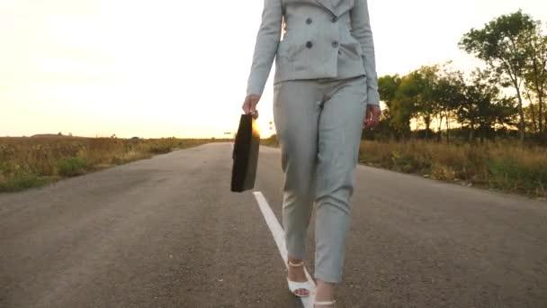 Busines swoman nese v ruce černou aktovku s dokumenty, Žena v lehké sako, kalhoty a bílá na vysokém podpatku boty procházky podél asfalt s označením, pohled z předu, zblízka