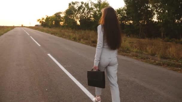 obchodnice s dlouhými tmavými vlasy nese v ruce černou aktovku, Žena procházky podél asfaltové mimo město v lehké sako a bílé vysokých podpatků, pohled zezadu