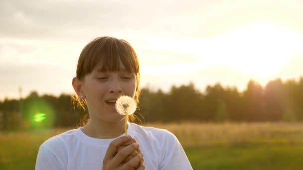 krásná dívka foukání na pampeliškového chmýří pomalu letící vzduchem, pomalý pohyb