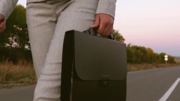 obchodnice s černou aktovkou v ruce, jde v kalhoty a bundu na asfaltu, zblízka