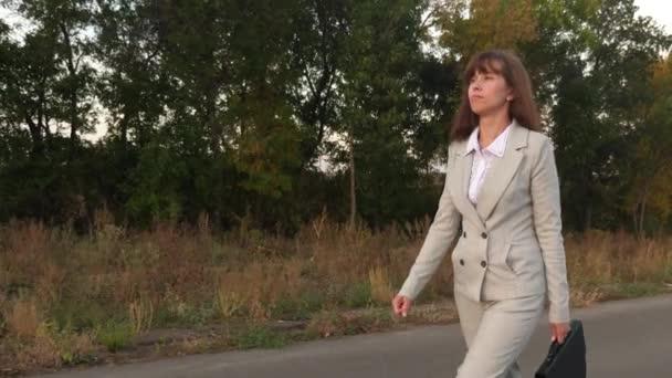 obchodní žena s černou aktovkou v ruce, jde v kalhoty a bundu na asfaltu mimo město, zblízka