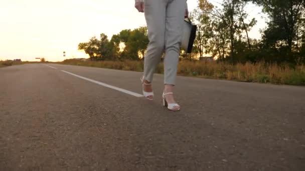 Geschäftsfrau trägt schwarze Aktentasche in der Hand. Frauenfüße in weißen Schuhen und Hosen stehen auf Asphalt.