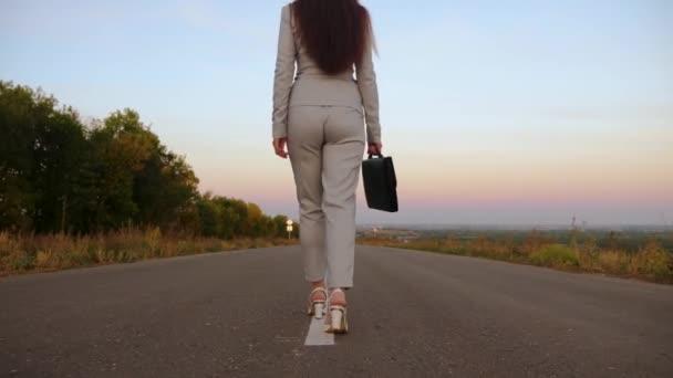 žena chodí po asfaltu mimo město nosí kalhoty a bundu a bílé boty s vysokými podpatky, podnikatelka nese černou aktovkou v ruce