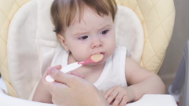 Little baby eats porridge from spoon, laugh and smiles sitting on highchair in kitchen. First feeding of babies. Play.