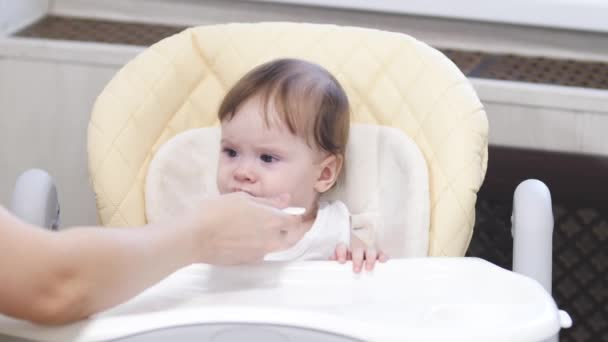 Baby eats porridge from spoon, spits and smiles sitting on highchair in kitchen.