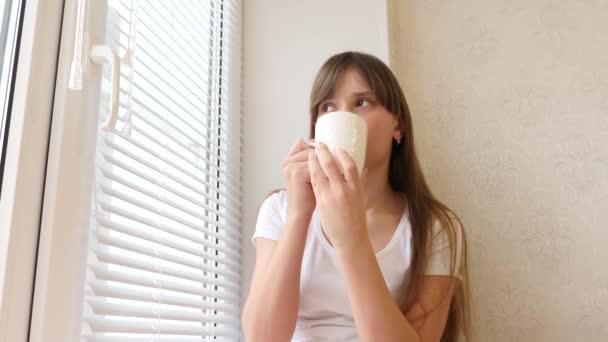 Krásná dívka s šálkem horkého čaje, sedět na parapetu u okna a usmívá se.