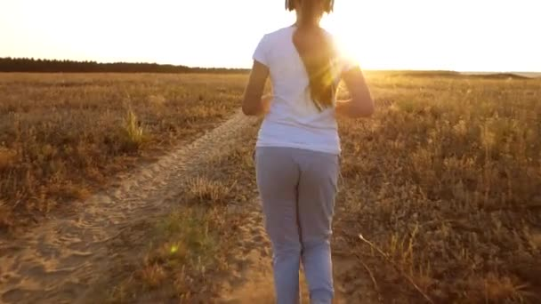 Beautiful girl doing sports exercises at sunset in countryside. girl in headphones runs along the road and listens to music. view from back