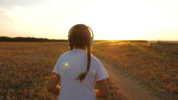 teenager girl trains at sunset and listens to music, sports girl in headphones does jogging.