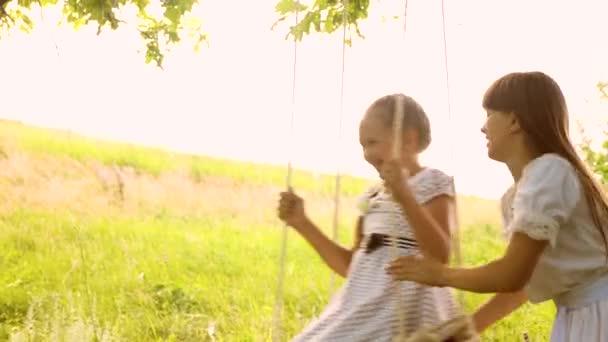 šťastná, že děti houpat na houpačce v parku, sestry jsou šťastné a rozesmáté. Zpomalený pohyb