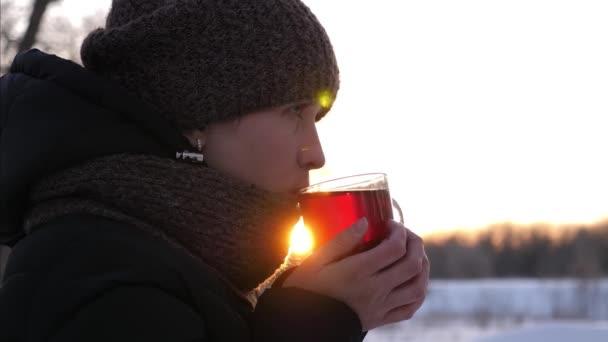 gyönyörű lány ital forró tea neki üveg poharat a naplemente, park télen. lány felmelegíti a keze a pohár kávét a téli erdő