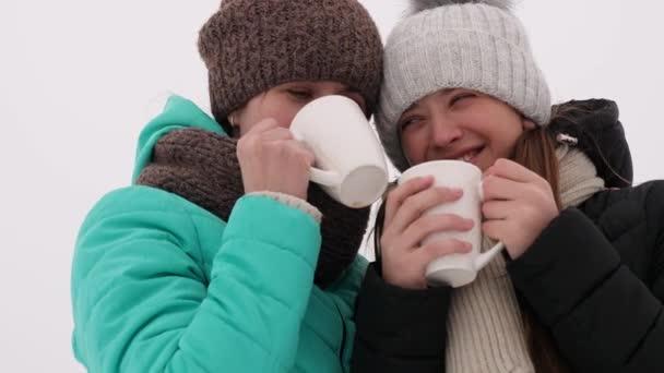 Happy girls pít kávu bílé sklo v zimě parku. Máma a dcera dospělých smát a usmívat na mrazivý Štědrý den. detail.