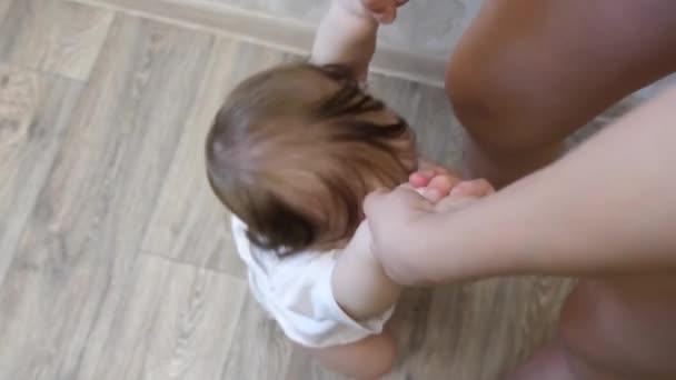 malé dítě si hraje s jeho mámou, drželi se za ruce, skákání a směje se do dětského pokoje