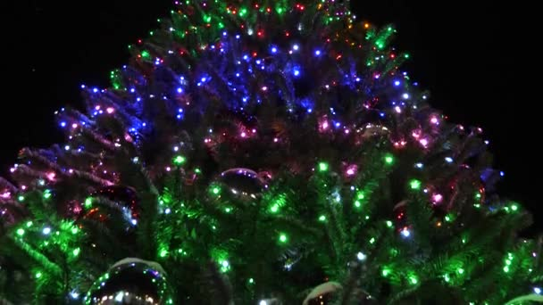 shining high Christmas fir-tree decorated with garlands and multi-colored balls against the night sky. little snow falls