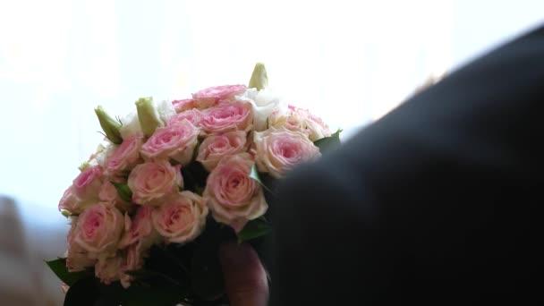 různobarevné růží v rukou člověka.