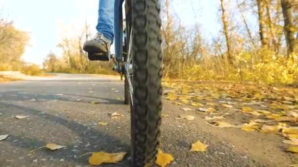 jízdní kolo s chrániči, detail. nohy dívky tlačí kolo pedály. jízdu na kole na asfaltovou silnici