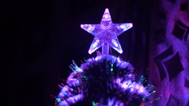 Stella di Natale si illumina con luci colorate sullalbero di Natale nella stanza dei bambini, lalbero di nuovo anno è decorato con gerland e lampeggia in blu e rosso