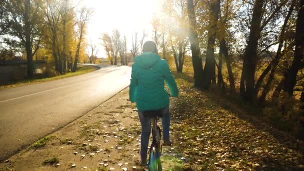 Mladá dívka na koni kolo na straně silnice na podzimní cestu. Zpomalený pohyb
