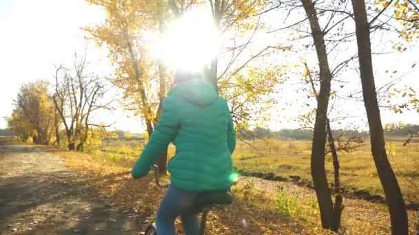 mladá dívka v růžové sako, jízdě na kole, ozářená paprsky slunce v podzimním parku. Zpomalený pohyb.