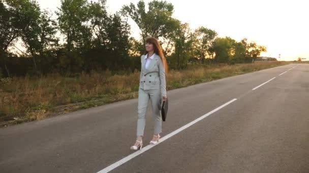 obchodní žena s černou aktovkou chodí ve světle barvy a bílé boty s vysokými podpatky jde mimo město po asfaltu s bílými znaky