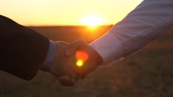 dva podnikatelé potřesení rukou při západu slunce. detail