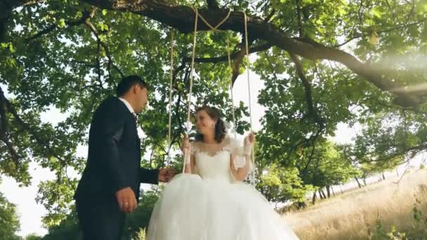 Happy young couple bride and groom in wedding dress swinging on swing in park. swings on branch of an oak in summer forest and a couple in love. close-up